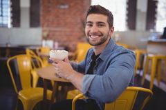 Portrait of smiling handsome man holding fresh coffee cup at cafe. Portrait of smiling handsome man holding fresh coffee cup while sitting on chair at cafe Royalty Free Stock Images