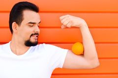 Portrait of a smiling handsome man with moustache and beard keeping an orange on his biceps muscle against coloured wall. royalty free stock photo