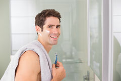 Portrait of smiling handsome man shaving in bathroom. Side view portrait of a smiling handsome young man shaving in the bathroom Royalty Free Stock Photo