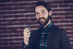 Portrait of smiling handsome man smoking pipe Stock Photography