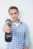 Portrait of a smiling handsome young handyman holding drill Royalty Free Stock Photography