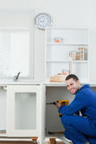 Portrait of a smiling handyman fixing a door Royalty Free Stock Photo