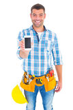 Portrait of smiling handyman showing mobile phone Royalty Free Stock Photo