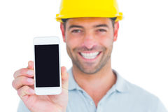 Portrait of smiling handyman showing smart phone Stock Photos