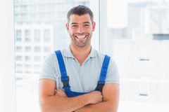 Portrait of smiling handyman standing arms crossed in office. Portrait of smiling handyman in overalls standing arms crossed in bright office Stock Photo