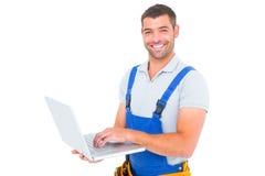 Portrait of smiling handyman using laptop Royalty Free Stock Images