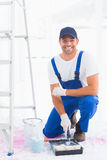 Portrait of smiling handyman using paint roller in tray stock photo
