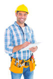 Portrait of smiling handyman writing on clipboard. Over white background Royalty Free Stock Photo