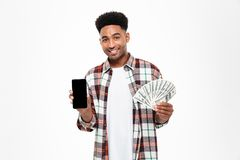 Portrait of a smiling happy african man. Holding bunch of money banknotes and showing blank screen mobile phone isolated over white background royalty free stock photography
