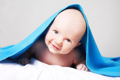 Portrait of a smiling happy baby boy having fun. Portrait of a smiling happy baby boy under blue blanket having fun. Studio indoors shoot royalty free stock images