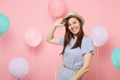 Portrait of smiling happy beautiful young woman wearing straw summer hat and blue dress on pastel pink background with stock photo