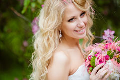 Portrait of a smiling happy bride blonde with pink bouquet royalty free stock images