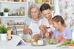 Portrait of smiling happy family cooking together. Smiling happy family cooking together at kitchen stock photography