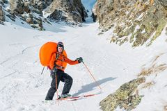 Portrait of a smiling happy freeride backcountry skier with an opened avalanche dowel abs in a backpack. Portrait on a background of a high-mountainous rocky stock photography