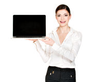 Woman holds laptop with blank screen Royalty Free Stock Photos