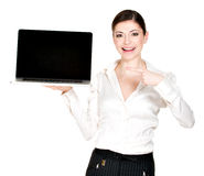 Woman holds laptop with blank screen Stock Photo