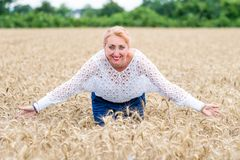 Portrait of a smiling happy woman in a ripe wheat field. Spread arms royalty free stock photography