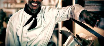 Portrait of smiling head chef. Standing in commercial kitchen stock photos