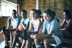 Portrait of smiling high school kids sitting on bench royalty free stock photography