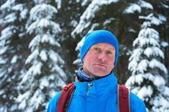Portrait of smiling hiker in cloudy winter day. Portrait of smiling hiker on the background of the snow covered fir trees, in the cloudy winter day Stock Images