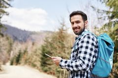 Portrait of smiling hiker using mobile phone during hiking trip royalty free stock photography