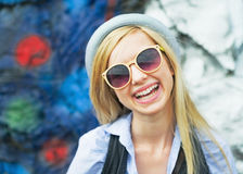 Portrait of smiling hipster girl wearing sunglasses outdoors. Portrait of smiling hipster girl  in hat wearing sunglasses outdoors Royalty Free Stock Photo