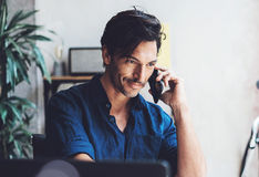 Portrait of Smiling Hispanic businessman working contemporary mobile computer while sitting at the wooden table at sunny Royalty Free Stock Photos