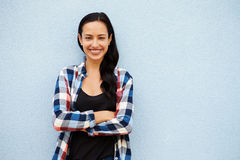 Portrait of smiling Hispanic woman against grey wall Stock Photos