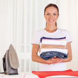 Portrait of smiling housewife ironing clothes. Stock Photos