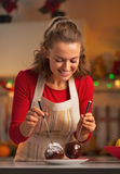 Portrait of smiling housewife making apple in chocolate glaze Stock Photos