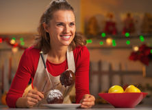 Portrait of smiling housewife making apple in chocolate glaze Stock Images