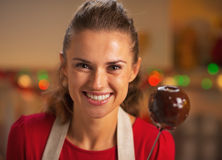 Portrait of smiling housewife showing apple in chocolate glaze Royalty Free Stock Photo