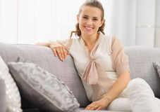 Portrait of smiling housewife sitting on couch Stock Photo