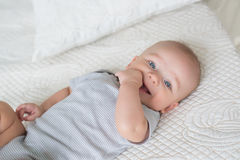 Portrait of smiling infant on a bed. Portrait of smiling infant on bed Royalty Free Stock Photography