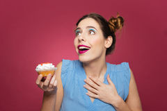 Portrait of smiling inspired young woman with cupcake. Over pink background Royalty Free Stock Photography