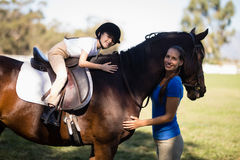 Portrait of smiling jockey and girl embracing horse. At paddock Royalty Free Stock Images