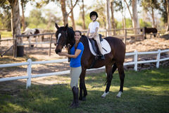 Portrait of smiling jockey and girl with horse. On field at paddock Royalty Free Stock Photography