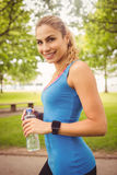 Portrait of smiling jogger woman holding water bottle Royalty Free Stock Photography