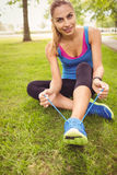 Portrait of smiling jogger woman tying shoelace Stock Photography