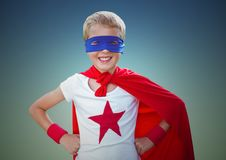 Portrait of smiling kid wearing red cape and blue mask standing with hand on hip against clear sky Royalty Free Stock Images