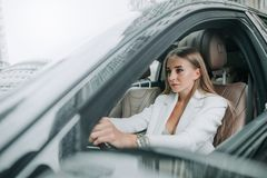 Glad pretty girl situating in contemporary car Royalty Free Stock Photos