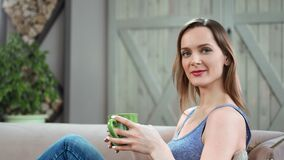 Portrait of smiling lady posing with mug at comfortable couch. Shot on RED Raven 4k Cinema Camera