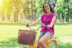 Portrait of smiling lady on yellow bicycle in the park Royalty Free Stock Photography