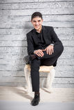 Portrait of smiling latin man sitting on chair against wooden wa Stock Photos