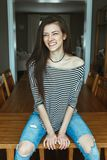 Caucasian young beautiful woman model with messy long hair in ripped blue jeans and striped t-shirt sitting on table Royalty Free Stock Photography