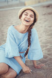 Portrait of smiling laughing white Caucasian brunette woman with tanned skin in blue dress and straw hat sitting on sand beach Royalty Free Stock Photo