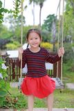Portrait of smiling little Asian child girl play and sitting on the swing in the nature park royalty free stock photo