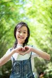 Portrait of smiling little asian girl gesturing heart shape with hands on bamboo forest,green nature background,happy people. Concept stock photography