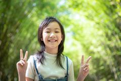 Portrait of smiling little asian girl shows a gesture of two fingers on bamboo forest,green nature background,happy people concept stock photography