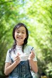 Portrait of smiling little asian girl shows a gesture of two fingersKorea finger heart and look at the camera on bamboo forest, stock images
